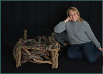 Basket artist Tina Puckett with her custom built, custom-woven end table Swirls of Pastel