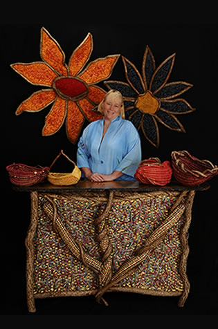 Master basket weaver Tina Puckett pictured with some of her hand-crafted woven works