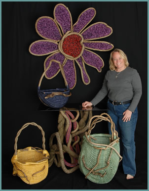 American master weaver Tina Puckett pictured with some of her baskets, a woven flower sculpture, and a woven pedestal table